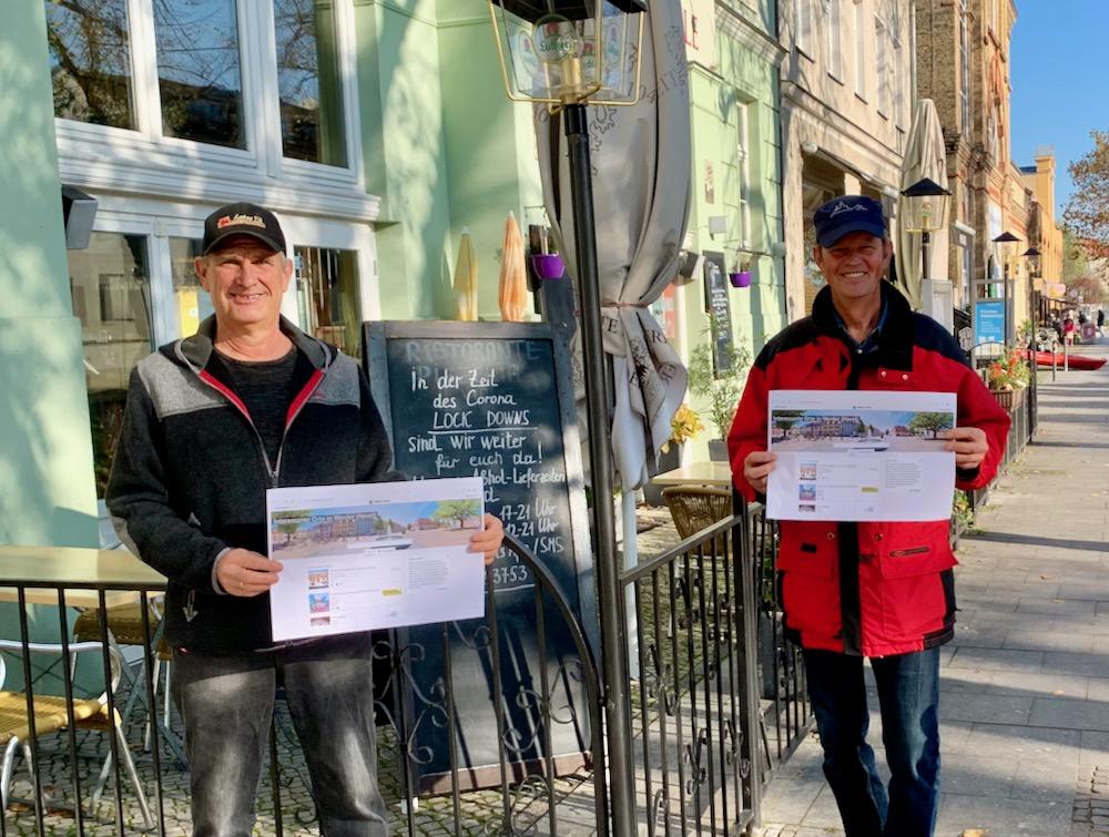 Dirk Lutze und Karsten Perenz vor einem Restaurant mit einem Symbolbild der Internetplattform. (Unter den Linden, Werder (Havel))